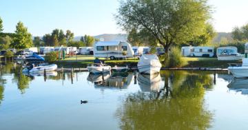 Campingplatz in Thüringen mit mehreren Wohnwagen, Zelten und Booten.